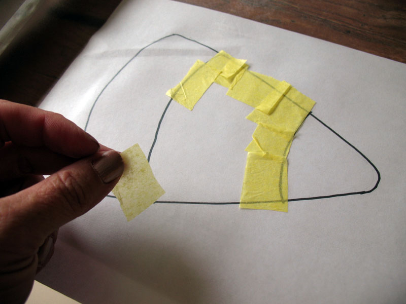 Using the pattern underneath the film as a guide, begin by placing yellow tissue paper squares onto the middle section of the candy corn.