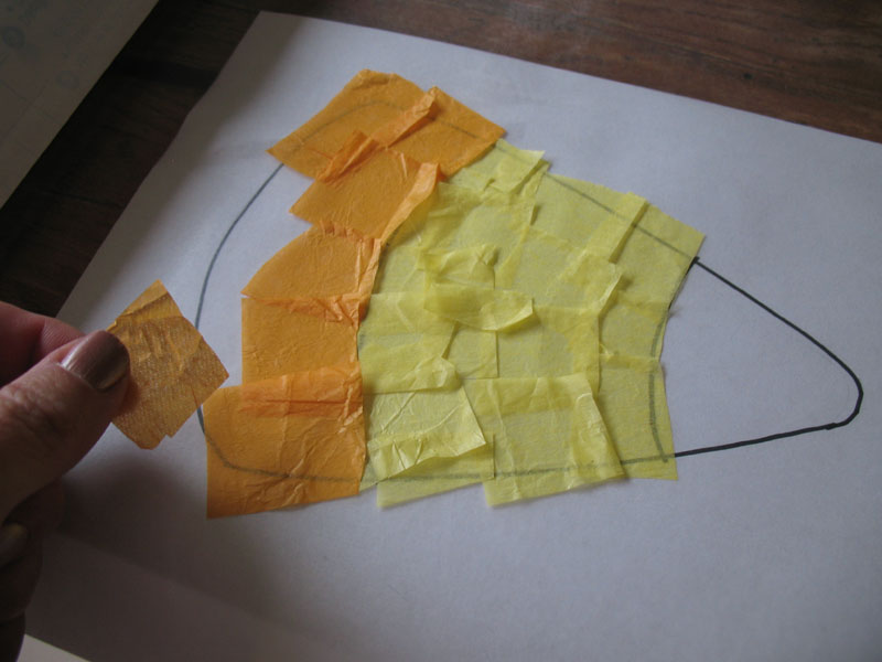 Next, use orange tissue paper to cover the bottom section of the candy corn.