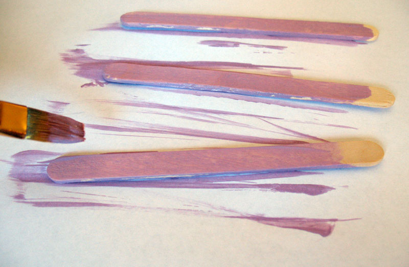 Paint the craft sticks purple and let dry.