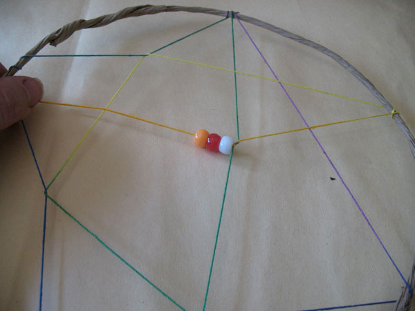 Thread on 2-3 colorful beads, stretch and wrap the string again.