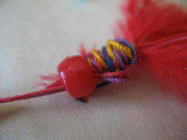 Slide a bead down onto the feather end to secure.