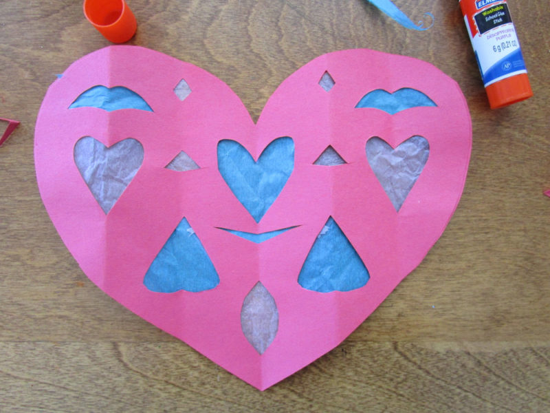 Glue other paper heart cutout. Faux Stained Glass Hearts Lesson Plan. KinderArt.com