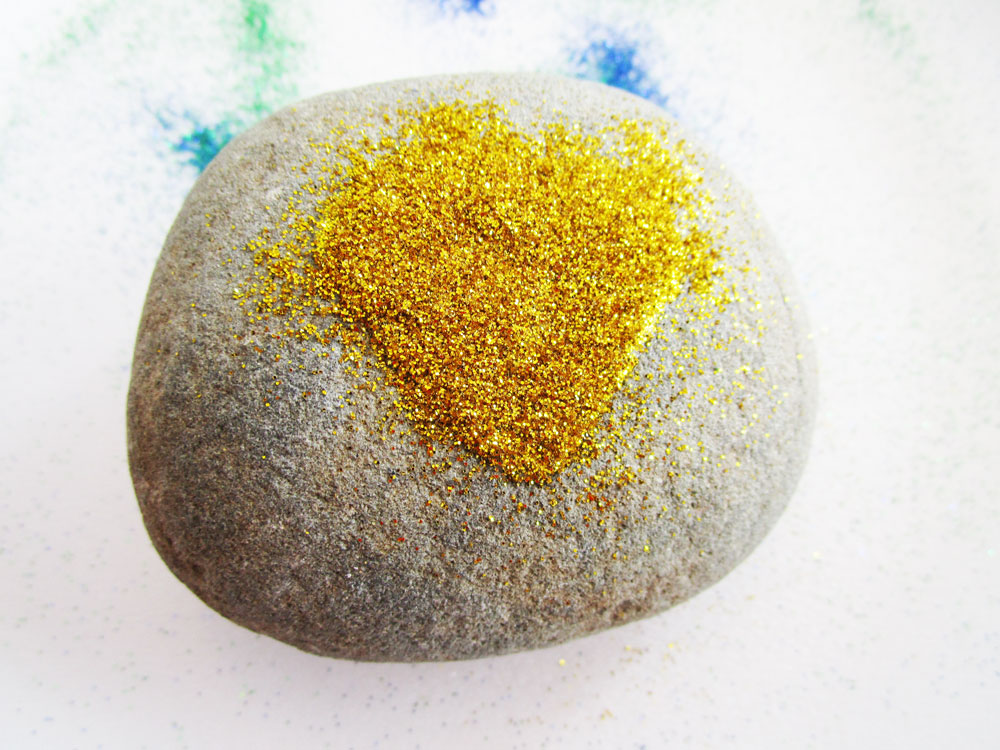 Sprinkle glitter on the rock.