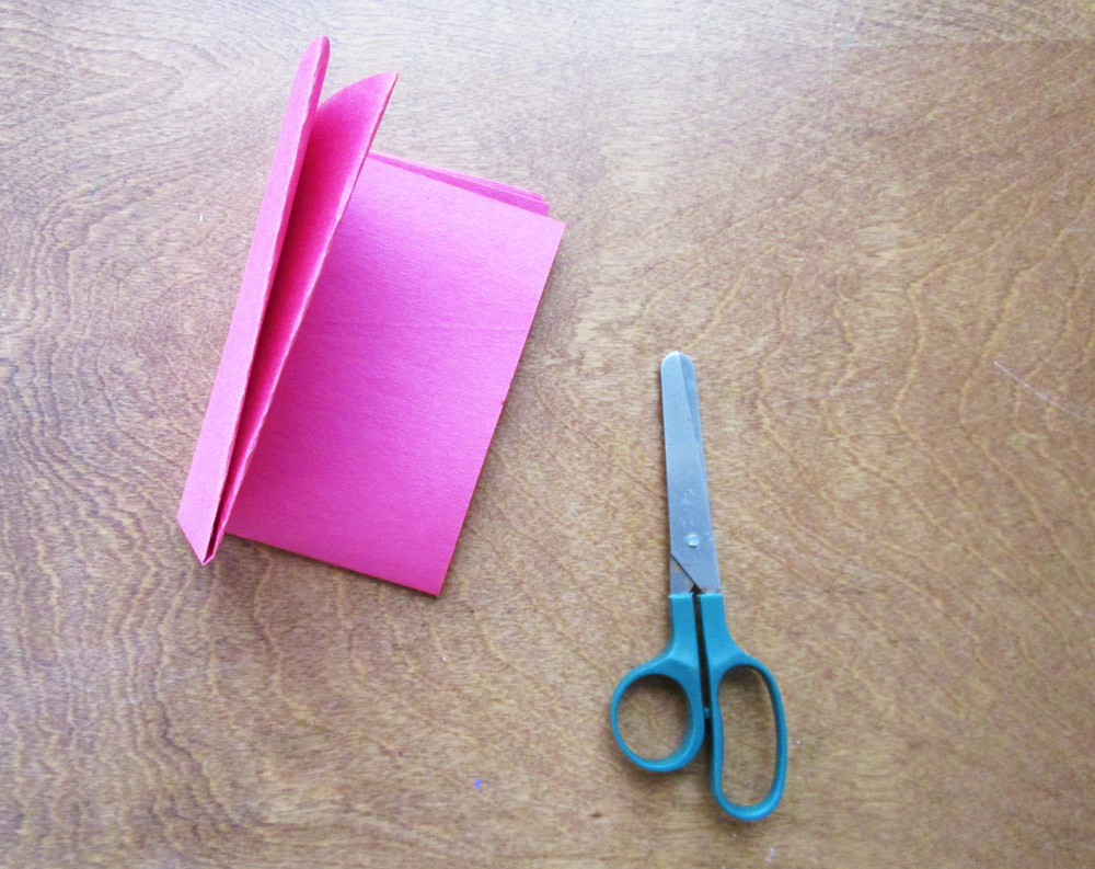 Fold a piece of red construction paper in half, three times.