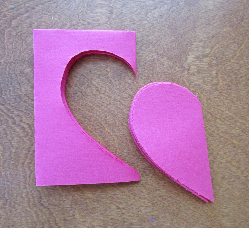 Cut a half heart shape out of the folded paper, making sure to cut at the folded edge.