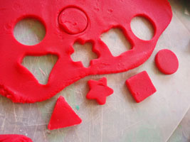 Cutting the play dough with cookie cutters.