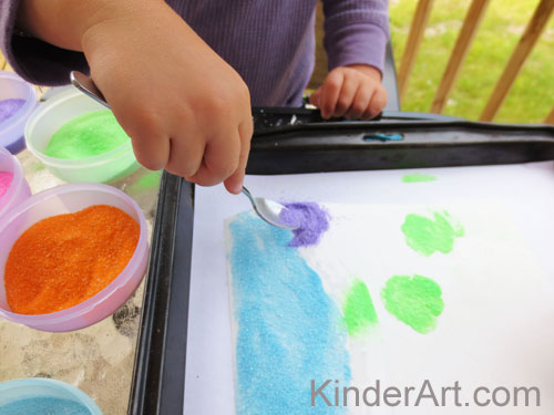Add sand to the paper with spoons.