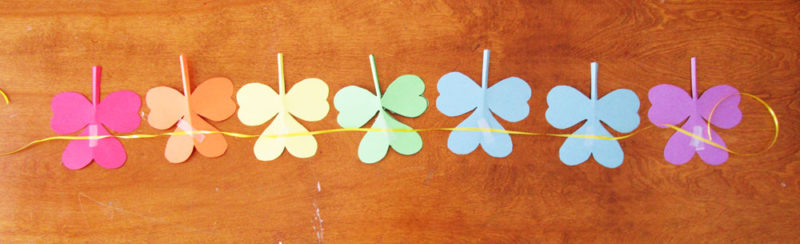 Once you have a number of shamrocks cut out, arrange them on a table and - using tape - attach a ribbon to the backs.