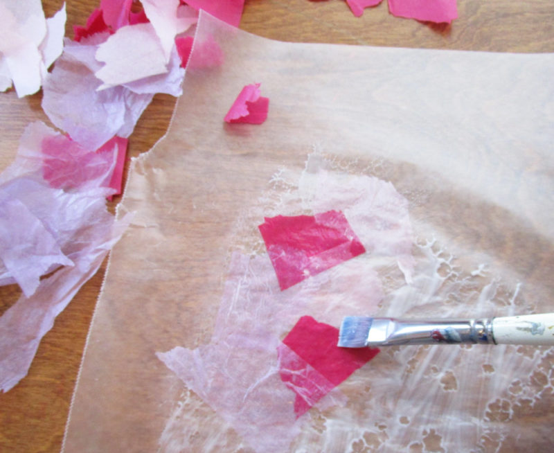 Glueing the tissue paper onto wax paper. Faux Stained Glass Hearts Lesson Plan. KinderArt.com
