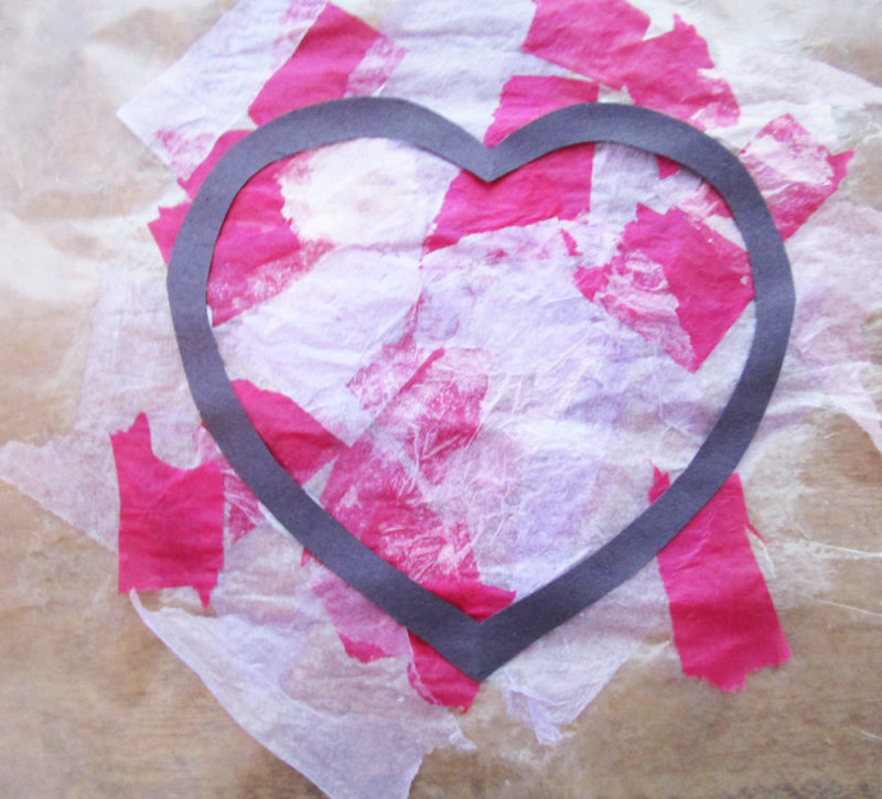 Place construction paper heart onto tissue paper and glue. Faux Stained Glass Hearts Lesson Plan. KinderArt.com
